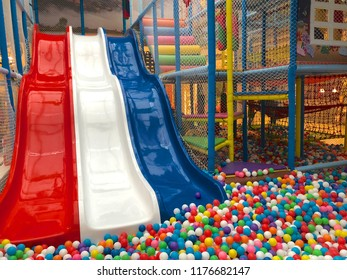 Modern children playground indoor. Inside the beautiful kids playground with a slide. Plastic dry pool with colorful balls for playing. Colorful plastic gum balls background in kid playroom