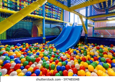 Modern children playground indoor. Inside the beautiful kids playground with a slide. Plastic dry pool with colorful balls for playing.