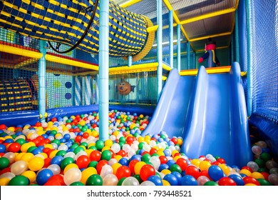Modern children playground indoor. Inside the colorful plastic structure for active games and development of motor skills. Pool with colored balls and slide. Kids playground for gym in kindergarten.