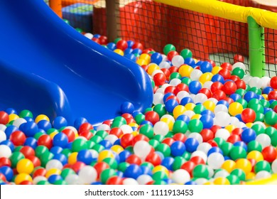 Modern children playground interior. Colored plastic balls pool with a blue hill. Selective focus