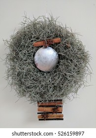 Modern Christmas wreath hanging with spanish moss, silver bauble, cinnamon sticks and aniseed