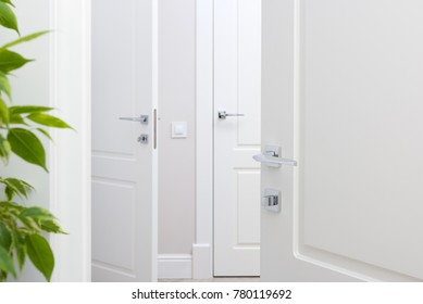 Modern chrome door handle on white door. Beautiful interior closeup. Handles for different areas