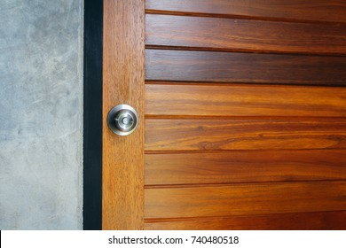 Modern chrome stainless steel door knob on a natural hardwood door, black wooden door frame with concrete wall. Concept for interior design and architecture.