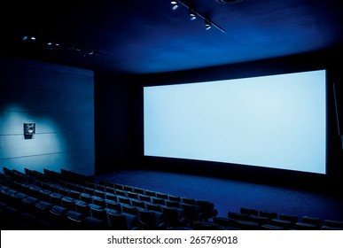 Modern cinema auditorium with white blank screen and luxury seats - dark movie theatre ready for projection