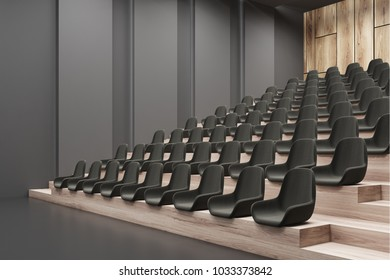 Modern cinema interior corner with dark walls, a concrete floor, and black chairs. 3d rendering mock up