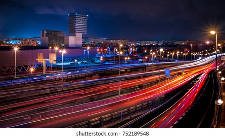 A modern city crossed by a highway at night with long exposure lights.