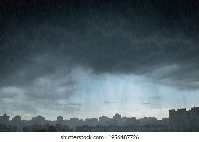 Modern city district under dramatic stormy rainy clouds. Shower rain over city. Downpour.