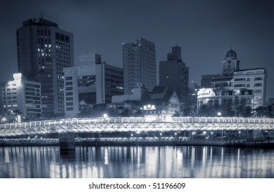 Modern city night with buildings and bridge near river.