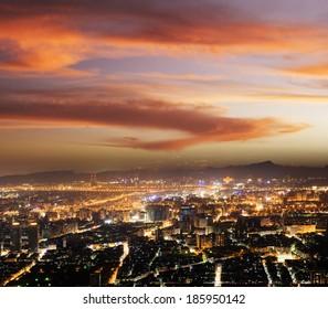 Modern city night under dramatic sky.