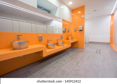 Modern city public toilet.  Orange wall with sinks and mirrors