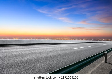 Modern city skyline and buildings with empty asphalt road at sunset