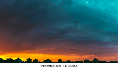 Modern city skyline. Dramatic colorful sunset sky with clouds over modern city rooftops wide panorama.