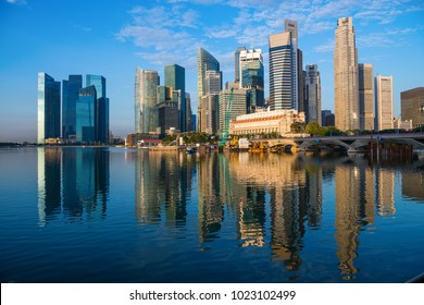 Modern city skyline with high skyscrapers in dark blue colors on Singapore Marina Bay waterfront at early sunrise morning time