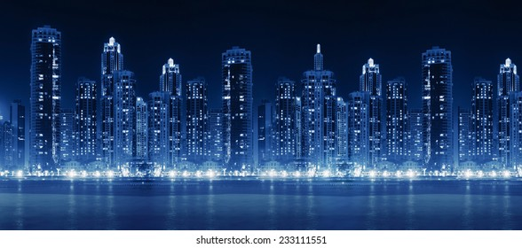 Modern city skyline at night with illuminated skyscrapers over water surface