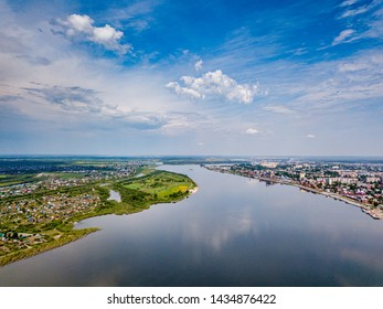 Modern city view. Town on river. Tomsk cityscape and Tom river from aerial view. Modern architecture. Beautiful sky. City downtown. Water resources. Siberia, Russia