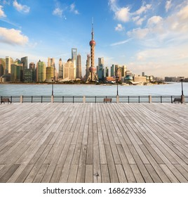 modern cityscape in shanghai,city skyline with wooden floor and railing on the waterfront