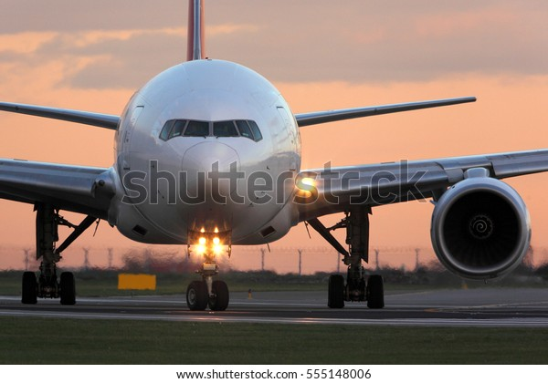 Modern civil passenger airliner taking off at airport during sunset.