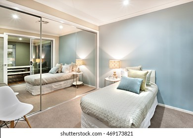 Modern and classic bedroom walls are light blue, which is illuminated in lights of the table lamp and one wall is totally covered with big mirrors. There is a chair behind the it and near the bed.