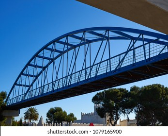 Modern classical design steel pedestrian bridge painted in blue over a busy street Orihuela Costa Spain