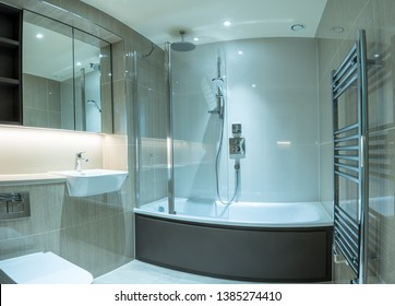 Modern clean bathroom in flat or apartment with bath shower, towel rail, sink and mirror cabinets