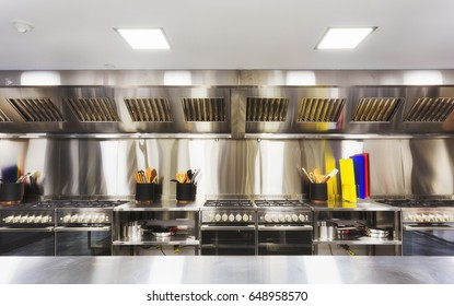 Modern clean equipped kitchen with stainless steel cook tops, cooking tables, utensils and small appliances.