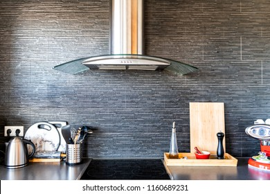 Modern, clean interior of kitchen with cooking utensils, tea pot or kettle, cutting board, coffee maker, electric stove, spices containers, stone wall backsplash and exhaust fan