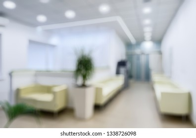 Modern clinic interior as creative abstract blur background. Clean hallway with plants in a small clinic. White and light interior of medical center or hospital. Inside the contemporary clinic.