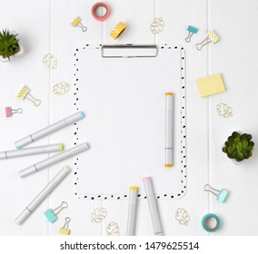 Modern clipboard with blank sheet and markers, clip, duct tape binders and plants on a white wooden background. Flat lay, top view art education concept.
