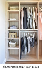 modern closet with row of cloths hanging in wooden wardrobe
