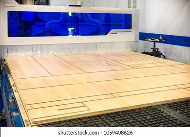 Modern CNC machining center for cutting a plywood sheet. The machine cuts out parts from a chipboard.