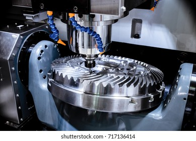 A modern CNC milling machine makes a large cogwheel. Accurate metal working. Shooting in real conditions, maybe some blurring and grain.