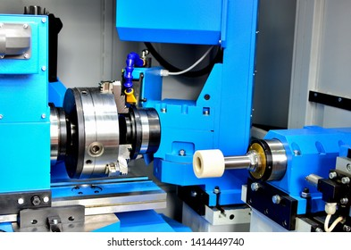 Modern CNC milling machine in the process of grinding a metal cylindrical shaft with internal thread. Production of spare parts for heavy-duty dump trucks. Small depth of field.