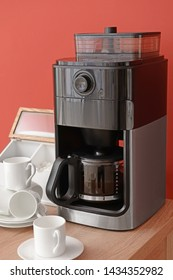 Modern coffee machine and cups on table against color background