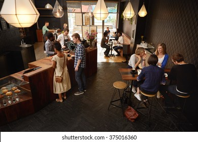 Modern coffee shop with baristas and various customers ordering
