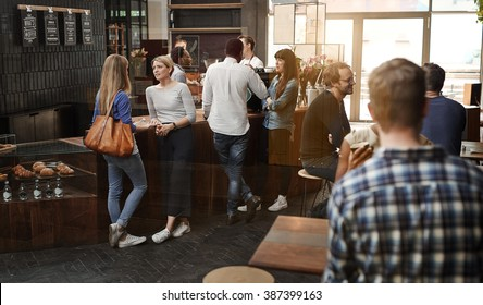 Modern coffee shop with customers standing at counter and sittin