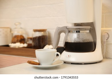 Modern coffeemaker and cup with cookie on table in kitchen