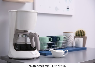 Modern coffeemaker and dishware on grey table in kitchen