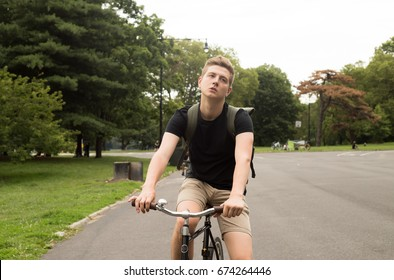 Modern college student ridinge bike in the park, photographed in Brooklyn, NY in 2017