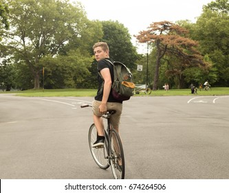 Modern college student ridinge bike in the park looking back, photographed in Brooklyn, NY in July 2017