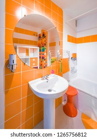 Modern and colorful bathroom. Interior decoration with orange towels and tiles and vintage furniture from the 70s