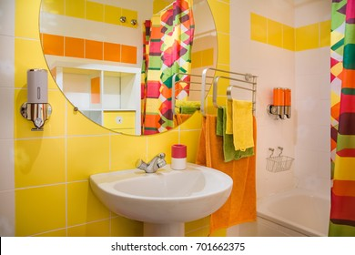 Modern and colorful bathroom. Yellow and orange towels and tiles.