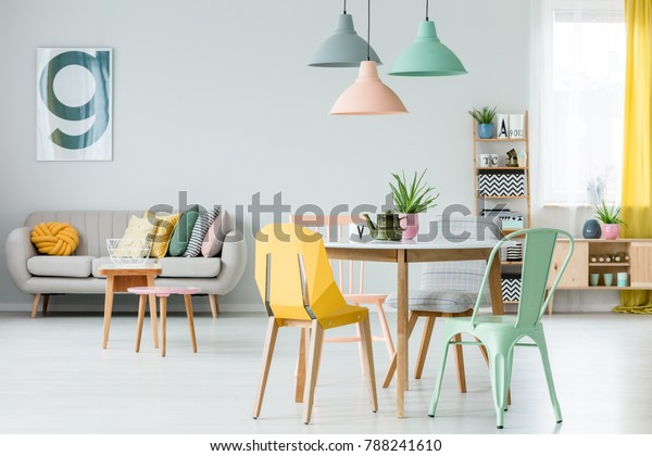 Modern colorful chairs at dining table under pastel lamps in living room interior with pillows on settee against wall with poster