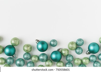 Modern, colorful Christmas holiday ornaments decorations in beautiful contemporary blue and green colors with sparkling glitter special effect on white background. Horizontal border banner image.