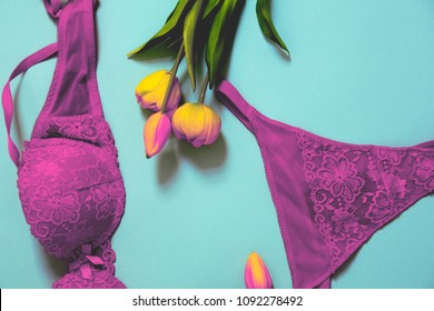 modern colors minimalis photo of sexy lace bra and panty and tulips on bright blue background