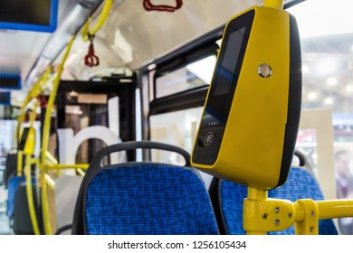 modern and comfortable City vehicle bus salon with empty passenger seats. Focus on yellow validator