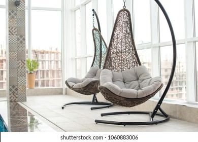 Modern comfortable hanging lounge chairs with soft pillows near panoramic window in recreation zone