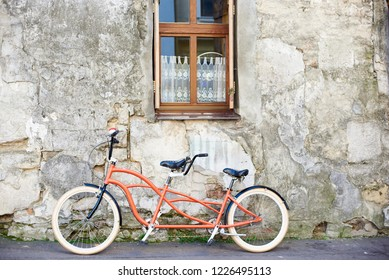 Modern comfortable orange tandem double bicycle with white wheels leaned to the old plastered cracked vintage house wall with lace curtain on small clean window on bright sunny summer day.