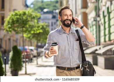 Modern communication. Cheerful adult man talking on phone and drinking coffee on the street