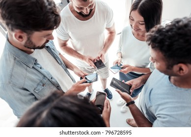 Modern communication. Top view on a group of millennial people standing in a circle and smiling while looking at screens of their phones.