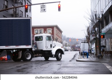 Modern compact powerful semi truck with a semi trailer frame fitted by a dark rubberized textile, turn at the crossroads with traffic lights in modern Portland downtown, delivering food and beverages.